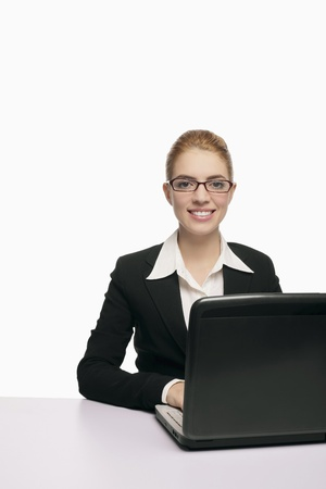 Businesswoman smiling while using laptop Stock Photo - 9956609