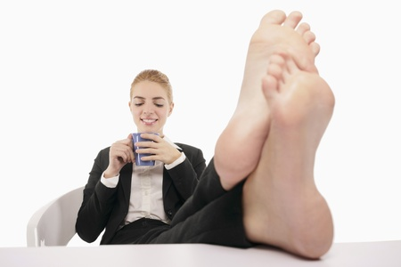 laziness: Businesswoman resting with her legs up on a table while drinking coffee