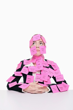 Businesswoman covered with adhesive notes looking up and thinking photo
