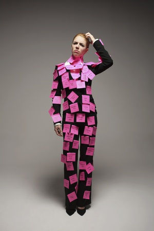 Businesswoman covered with adhesive notes scratching her head photo
