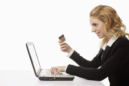 Businesswoman holding credit card while using laptop Stock Photo - 9957104