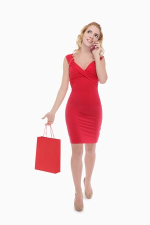 Woman talking on mobile phone while shopping photo