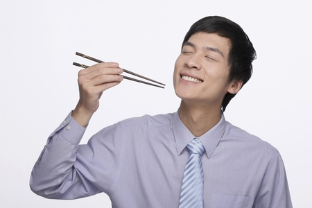 Businessman eating with chopsticks photo