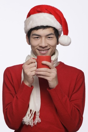 Man with santa hat holding a cup of hot coffee photo