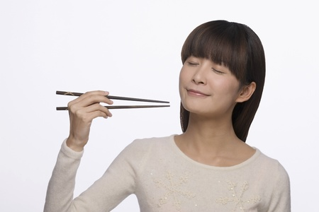 Woman eating with chopsticks photo