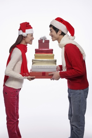joy of giving: Man and woman holding a stack of gift boxes Stock Photo