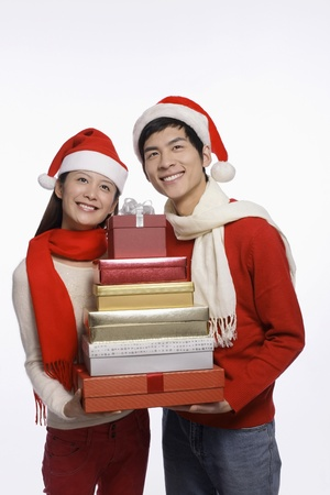 Man and woman holding a stack of gift boxes photo