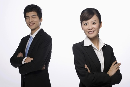 Businessman and businesswoman with their arms crossed Stock Photo