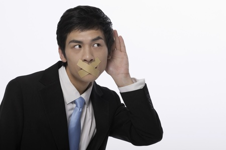 Businessman with his mouth taped, trying to listen to a conversation photo