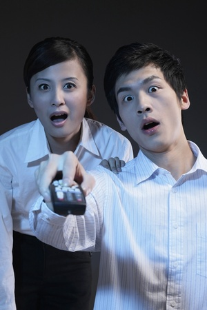 Man and woman in shock while watching television Stock Photo - 9957871