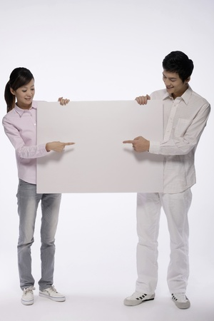 Man and woman holding and pointing at white placard photo