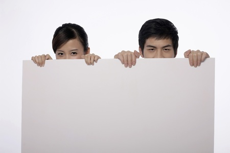 Man and woman hiding behind a white placard Stock Photo - 9957349