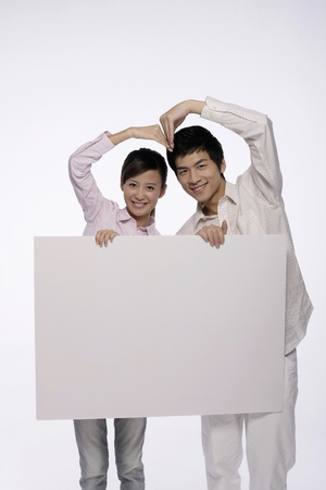 Man and woman  forming a love shape  while holding white placard photo
