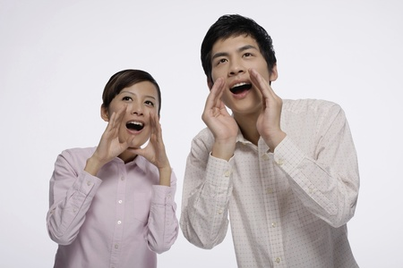 Man and woman with hands on mouth while yelling photo