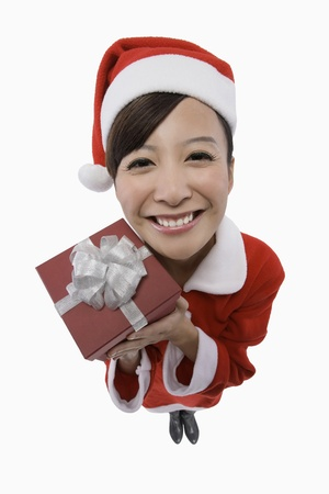 Woman in santa suit holding present photo