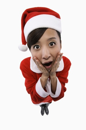 Woman in santa suit looking surprised photo