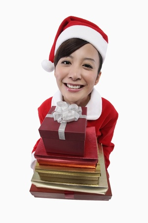 Woman in santa suit with a stack of gift boxes photo