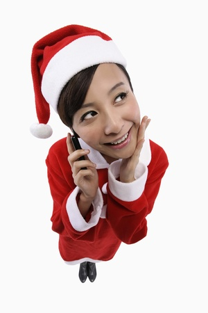 Woman in santa suit talking on the mobile phone photo