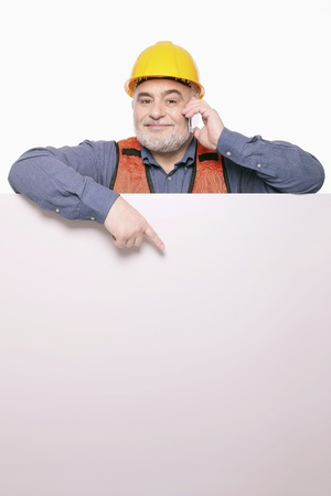 Man pointing at placard while talking on the mobile phone Stock Photo - 9957789
