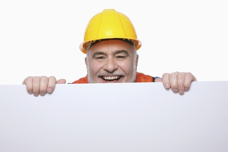 Man with hardhat peeping from behind a placard photo