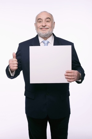 Businessman holding placard and showing thumbs up photo