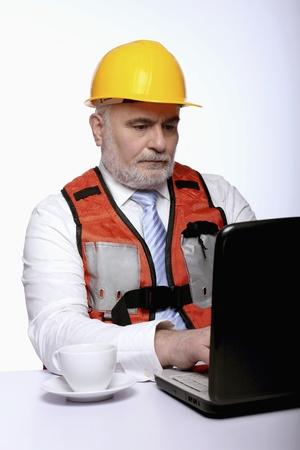 Man with hardhat using laptop photo