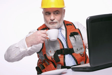 Man with hardhat drinking coffee while using laptop Stock Photo