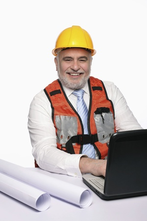 Man with hardhat smiling while using laptop