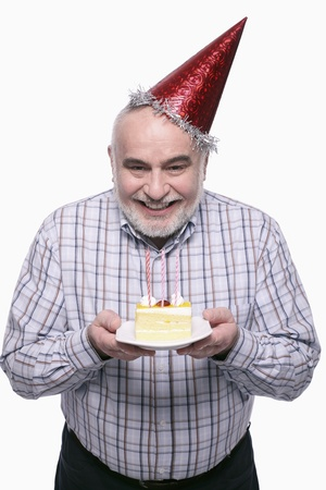 Man with party hat holding a plate of birthday cake Stock Photo - 9957849