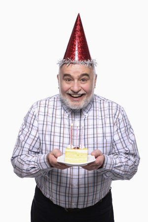 Man with party hat holding a plate of birthday cake Stock Photo