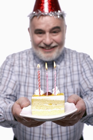 Man with party hat holding a plate of birthday cake photo