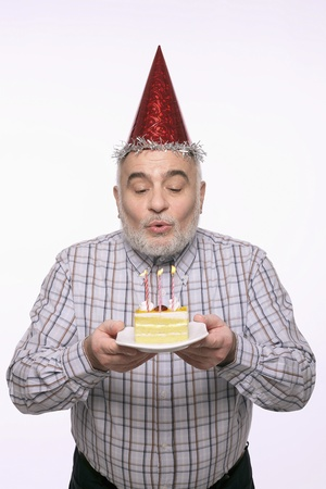 Man blowing the candles on birthday cake photo