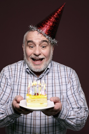 Man with party hat holding a plate of birthday cake Stock Photo - 9956889