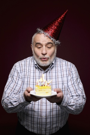 Man blowing candles on birthday cake photo