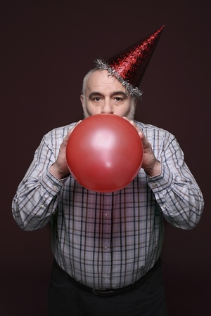 Man with party hat blowing balloon photo