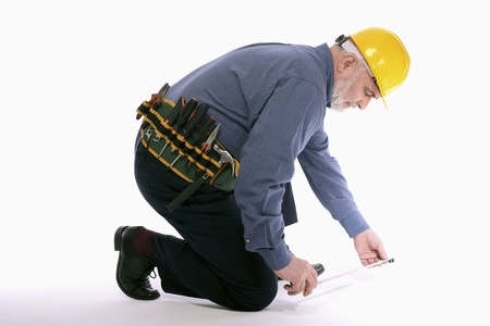 Man with hardhat measuring floor with tape measure photo