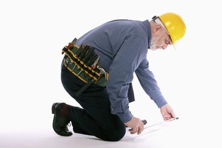 kneel down: Man with hardhat measuring floor with tape measure
