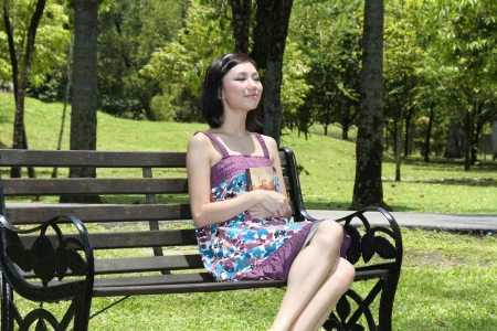 Woman with book sitting on the bench Stock Photo - 9957902