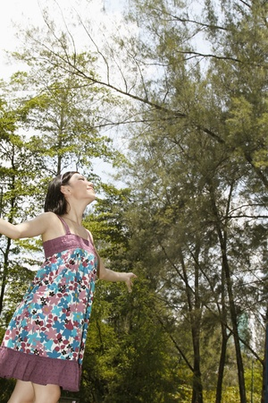 Woman with arms outstretched and eyes closed photo