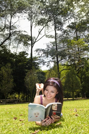 Woman lying on grass reading book photo