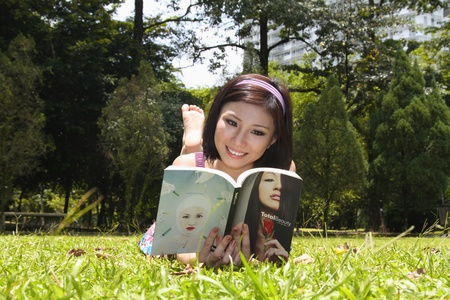 Woman lying on grass reading book Stock Photo - 9957876