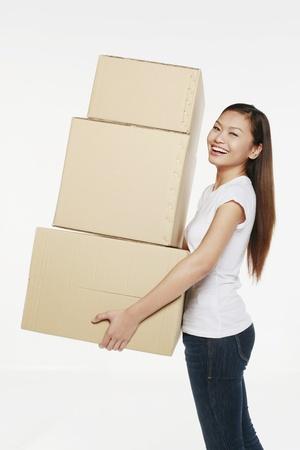 weitermachen: Frau tr�gt einen Stapel von Kisten
