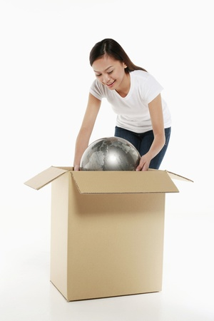 Woman packing globe into a box photo
