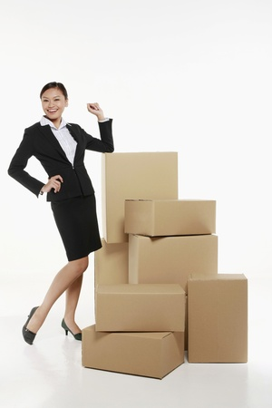 Businesswoman with a pile of boxes Stock Photo