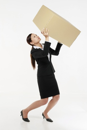 Businesswoman carrying a heavy box photo