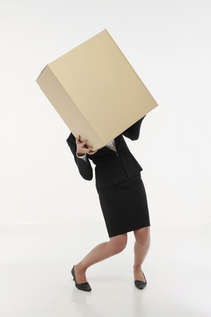 Businesswoman carrying a heavy box Stock Photo - 9957393