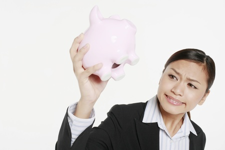 Businesswoman looking at piggy bank in frustration Stock Photo - 9957450