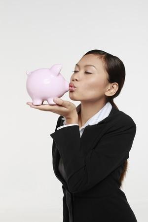 Businesswoman kissing piggy bank photo