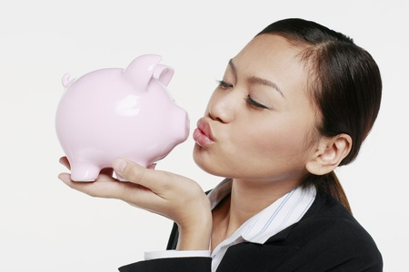 Businesswoman kissing piggy bank Stock Photo - 9957663