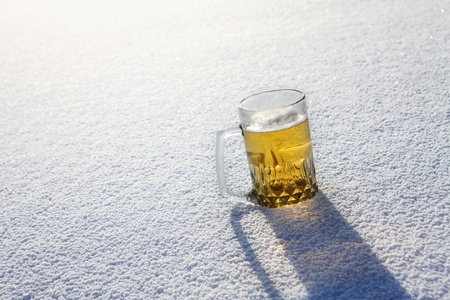 A glass of beer sitting in snow